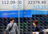 © Reuters. People walk past an electronic board showing Japan