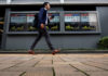 © Reuters. A passerby walks past an electronic boards Japan