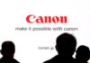 © Reuters. People are silhouetted against a display of the Canon brand logo at the CP+ camera and photo trade fair in Yokohama, Japan