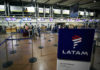 © Reuters. FILE PHOTO: Passengers wait to check in for their flights at the departures area of Latam airlines inside the international airport in Santiago