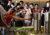 © Reuters. Woman points at the model of a residential compound by China Vanke as a sales agent introduces the property to the visitors at its showroom in Dongguan