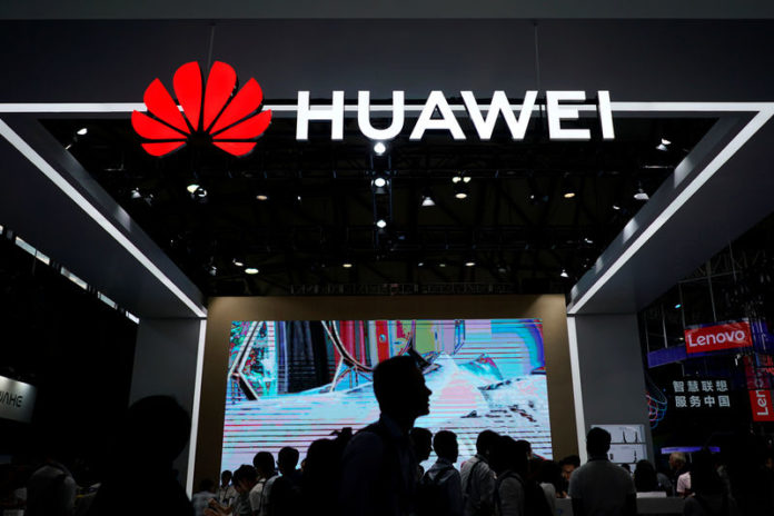 © Reuters. People walk past a sign board of Huawei at CES (Consumer Electronics Show) Asia 2018 in Shanghai