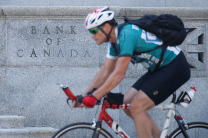 © Reuters. A cyclist rides past the Bank of Canada building