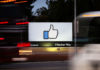 © Reuters. The entrance sign to Facebook headquarters is seen through two moving buses in Menlo Park