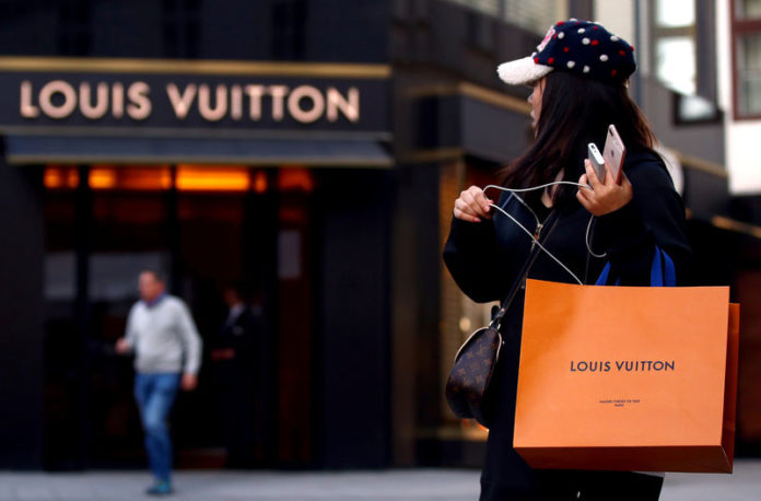 © Reuters. FILE PHOTO: Woman with a Louis Vuitton-branded shopping bag looks towards the entrance of a branch store by LVMH Moet Hennessy Louis Vuitton in Vienna