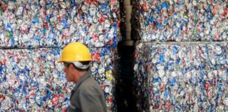 © Reuters. FILE PHOTO: A worker walks in front of compacted cans in an aluminium recycling plant in Ciudad Juarez