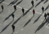 © Reuters. People cast long shadows in the winter sunlight as they walk across a plaza in the Canary Wharf financial district of London