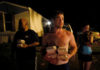 © Reuters. Chris Bailey holds hot food prepared by Operation BBQ Relief and distributed by 50 Star Search and Rescue in Panama City Beach