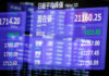 © Reuters. FILE PHOTO: Electronic board showing the Nikkei share average is seen as market prices are reflected in a glass window at the TSE in Tokyo