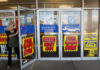 © Reuters. A woman walks out the door past signs advertising store closing signs Sears in New Hyde Park, New York