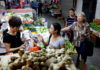 © Reuters. FILE PHOTO: People shop for vegetables at a wet market in Singapore
