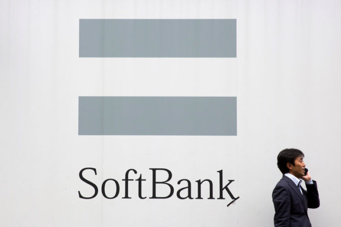 © Reuters. FILE PHOTO : A man talks on the phone as he stand in front of an advertising poster of the SoftBank telecommunications company in Tokyo