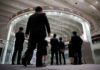 © Reuters. FILE PHOTO: Visitors look at the TSE bourse in Tokyo