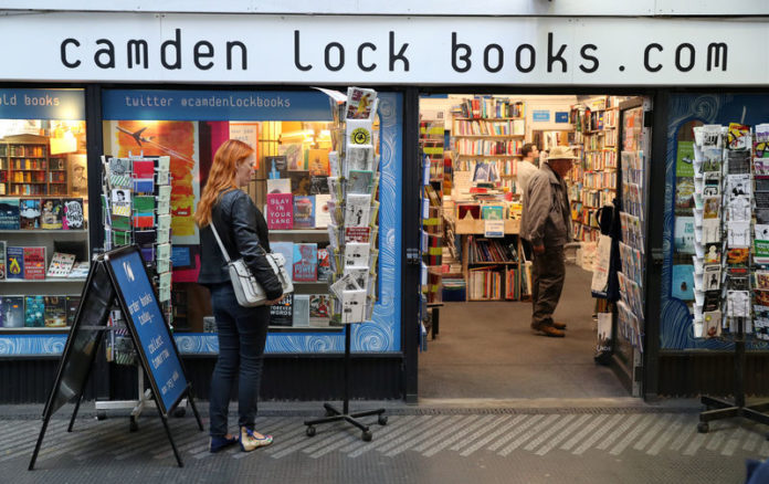 © Reuters. FILE PHOTO: A woman looks at gift cards outside Camden Lock Books shop, Old Street Station, London
