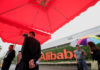 © Reuters. FILE PHOTO: People stand near a sign of Alibaba Group at its campus in Hangzhou