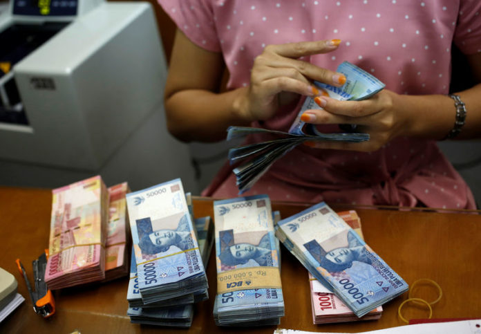 © Reuters. FILE PHOTO:  A teller counts Indonesian rupiah bank notes at a money changer in Jakarta