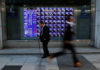 © Reuters. Passersby walk past in front of an electronic stock quotation board outside a brokerage in Tokyo