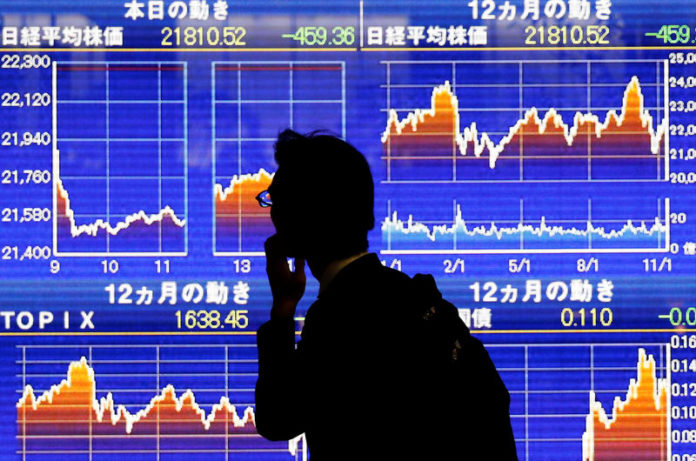 © Reuters. A man looks at an electronic stock quotation board showing Japan
