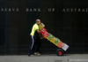 © Reuters. FILE PHOTO: File photo of a worker walking past the Reserve Bank of Australia (RBA) building in central Sydney