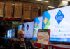 © Reuters. A man walks past television screens during the shopping season,