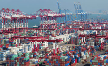 © Reuters. FILE PHOTO:  Containers and trucks are seen at a terminal of the Qingdao port in Shandong