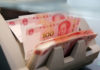 © Reuters. FILE PHOTO: Chinese 100 yuan banknotes in a counting machine while a clerk counts them at a branch of a commercial bank in Beijing