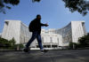 © Reuters. FILE PHOTO: A man walks past the headquarters of the People