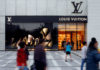 © Reuters. FILE PHOTO Pedestrians pass in front of a Louis Vuitton shop in Chengdu, Sichuan province, in China