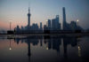 © Reuters. A security guard walks on the bund in front of the financial district of Pudong in Shanghai