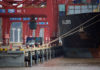 © Reuters. Trucks transport containers next to a container ship at a port in Zhoushan