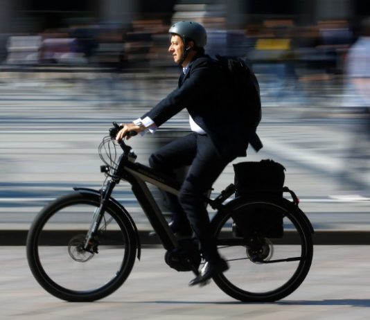 © Reuters. FILE PHOTO - A man rides an electric bicycle, also known as an e-bike, in downtown Milan