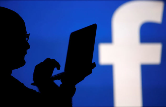 © Reuters. FILE PHOTO: A man is silhouetted against a video screen with an Facebook logo in this photo illustration in Zenica