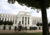 © Reuters. FILE PHOTO: A cyclist passes the Federal Reserve building in Washington, DC