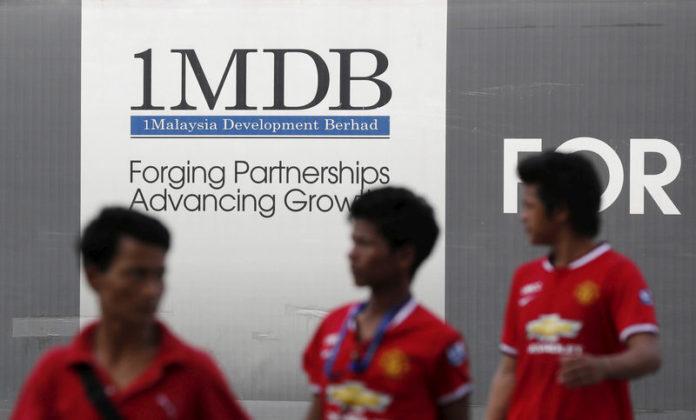 © Reuters. Men walk past a 1 Malaysia Development Berhad (1MDB) billboard at the fund