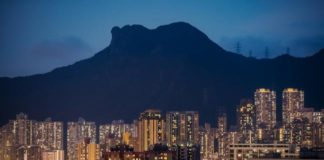 © Bloomberg. Residential buildings stand illuminated under Lion Rock at dusk in Hong Kong, China, on Saturday, July 21, 2018. Hong Kong