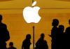 © Reuters. FILE PHOTO: Customers walk past an Apple logo inside of an Apple store at Grand Central Station in New York