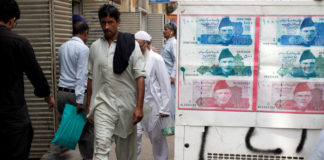 © Reuters. FILE PHOTO: Passersby walk past an advertisement board with photos of Pakistani rupee at a money exchange along a sidewalk in Karachi