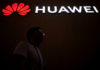 © Reuters. FILE PHOTO: A man walks past a sign board of Huawei at CES (Consumer Electronics Show) Asia 2018 in Shanghai