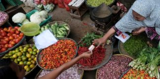 © Reuters. FILE PHOTO:  A vegetable seller reaches for money from a customer at a market in Jakarta