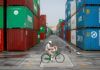 © Reuters. FILE PHOTO: A worker rides a bicycle in a container area at a port in Tokyo