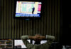 © Reuters. A man watches news on TV as he works on the floor of the Buenos Aires Stock Exchange