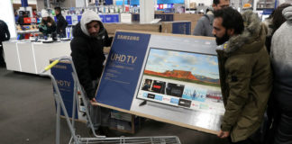 © Reuters. FILE PHOTO: People carry a television inside a Best Buy during a sales event on Thanksgiving day in Westbury, New York