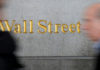 © Reuters. FILE PHOTO: People walk by a Wall Street sign close to the NYSE in New York