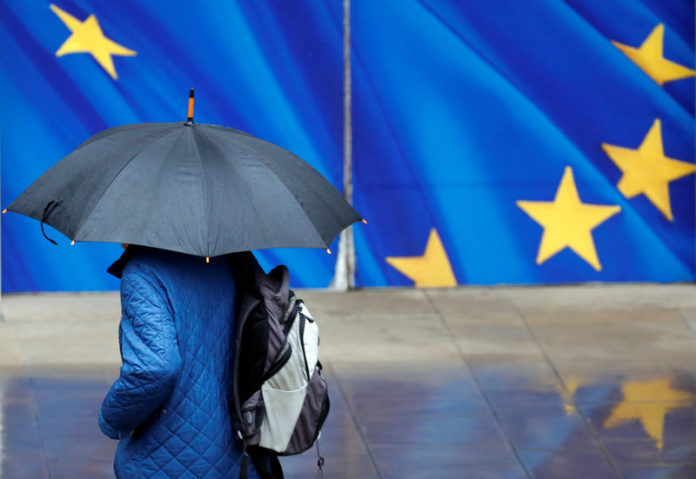 © Reuters. A man with an umbrella walks past the EU Commission headquarters in Brussels
