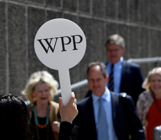 © Reuters. FILE PHOTO: An usher holds a baton to guide attendees towards the AGM of advertising agency WPP in London, Britain