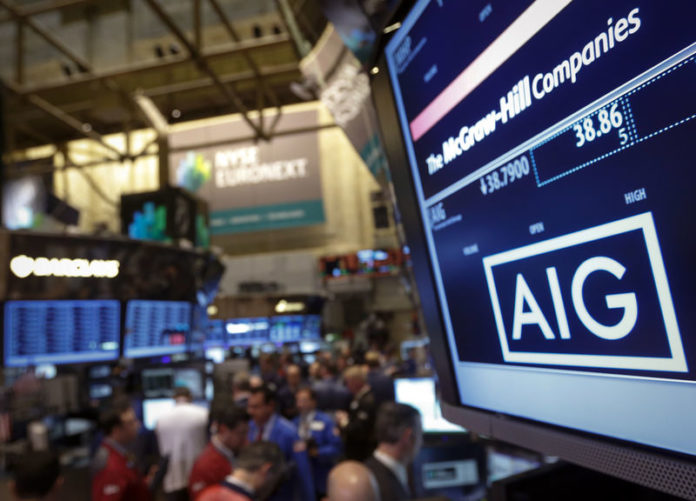 © Reuters. The American International Group, Inc. (AIG) stock ticker is seen on a monitor as traders work on the floor of the New York Stock Exchange