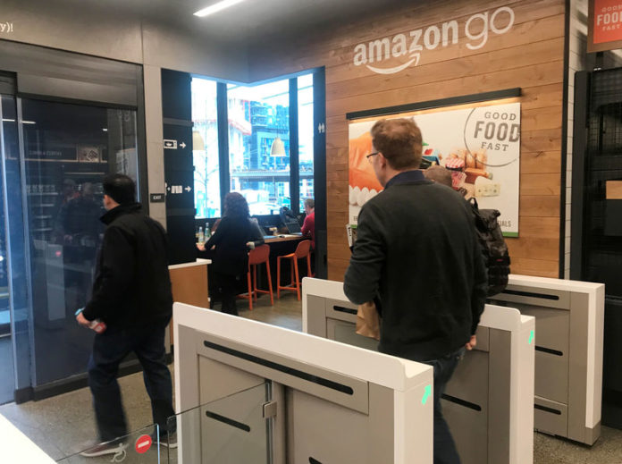 © Reuters. FILE PHOTO: A customer walks out of the Amazon Go store, without needing to pay at a cash register due to cameras, sensors and other technology that track goods that shoppers remove from shelves and bill them automatically after they leave, in Seattle