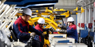 © Reuters. FILE PHOTO: Employees work on a drilling machine production line at a factory in Zhangjiakou