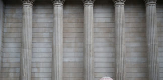 © Reuters. A pedestrian shelters under an umbrella in front of the Bank of England, in London