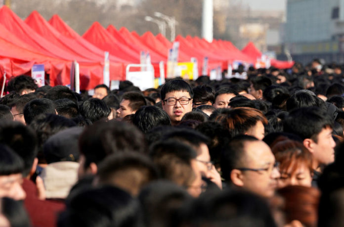 © Reuters. FILE PHOTO:  Job seekers crowd a job fair at Liberation Square in Shijiazhuang